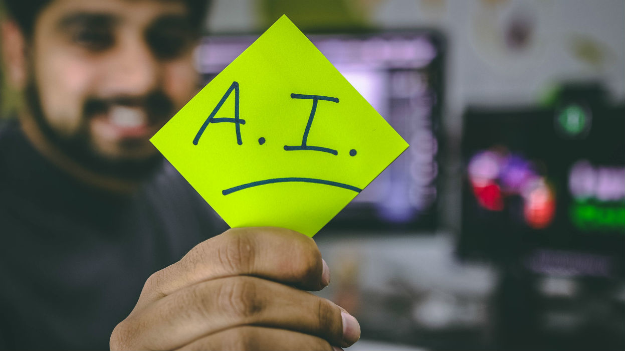student holding a yellow sticky note highlighting AI